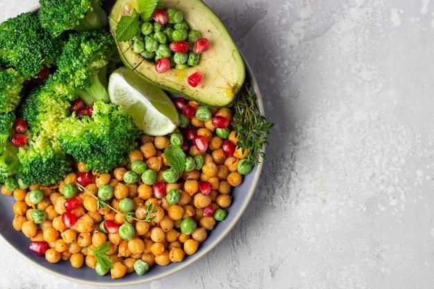 Pflanzliches mittagessen aus brokkoli, kichererbsen, avocado, erbsen, granatapfel, limette und minze
