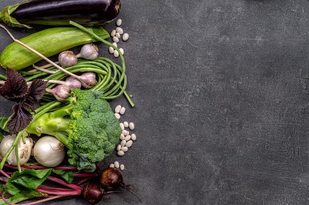 Pflanzliches vitaminset von auberginen, zucchini, grünen bohnen und brokkoli auf grauem tisch
