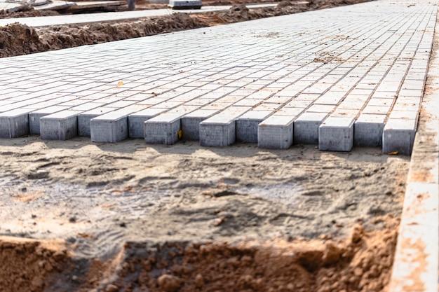 Pflasterreparatur und verlegung von pflastersteinen auf dem gehweg, gestapelte fliesenwürfel im hintergrund. verlegen von gehwegplatten in der fußgängerzone der stadt, sandfüllung. straßenfliesen und bordsteine.