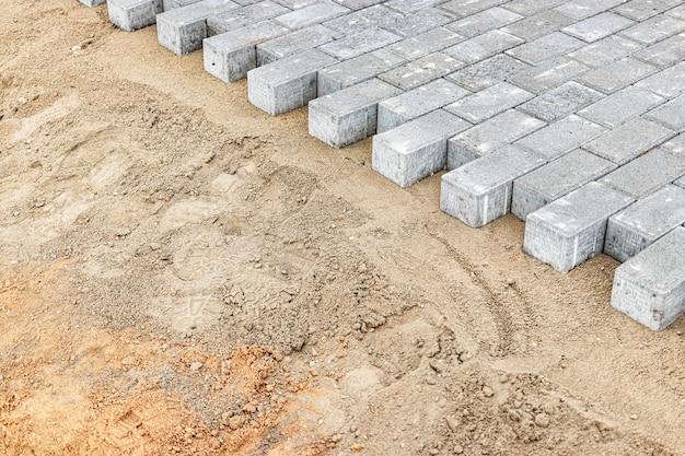 Pflasterreparaturen und pflasterplatten auf der vorbereiteten oberfläche, mit fliesenwürfeln im hintergrund. verlegen von gehwegplatten in der fußgängerzone der stadt. pflastersteine und bordsteine.