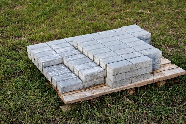 Pflastersteine auf einer palette, die für die installation auf einem grünen rasen vorbereitet ist. pflasterung der straße mit betonplatten.
