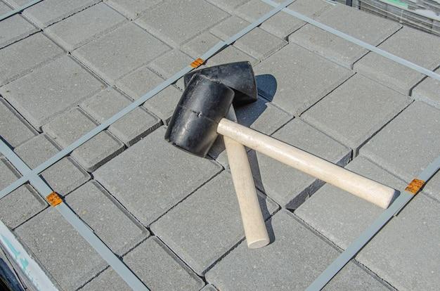 Pflastersteine, die hintergrund pflastern. installieren von werkzeugen gummihammer im vordergrund
