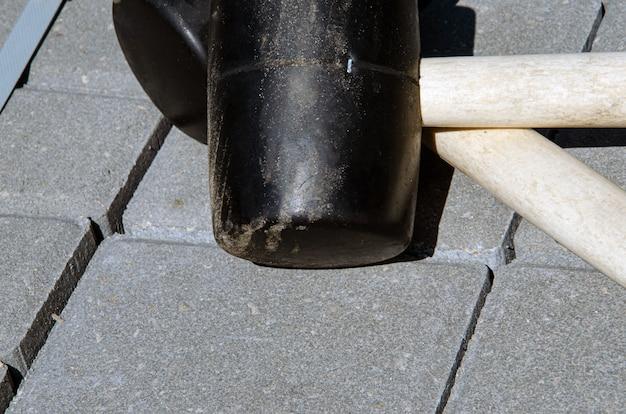 Pflastersteine pflastern. installieren von werkzeugen gummihammer im vordergrund