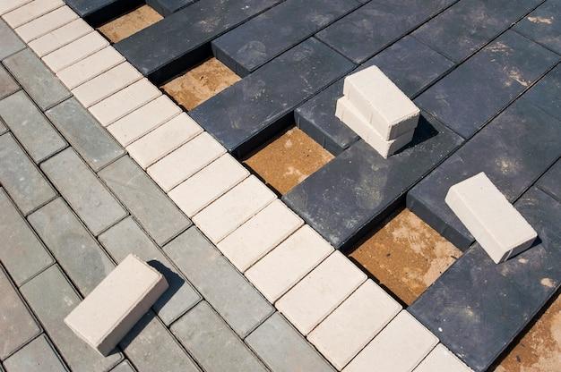 Pflastersteine werden auf ein erdfundament gelegt