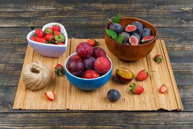 Pflaumen, erdbeeren und feigen in schalen