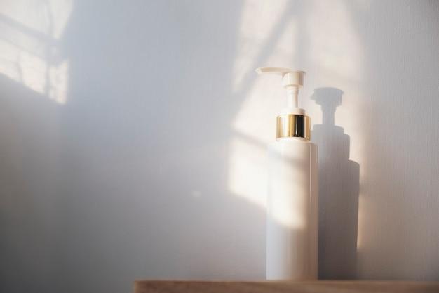 Pflaumenflasche händedesinfektionsmittel auf weiß und licht vom fenster