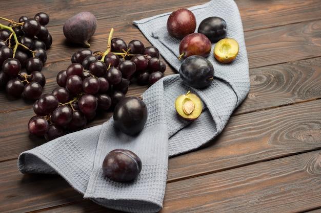 Pflaumenfrüchte auf grauer serviette. halbe pflaume mit grube. trauben schwarzer trauben auf dem tisch. dunkle holzoberfläche. draufsicht. speicherplatz kopieren