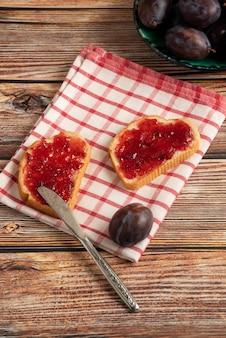 Pflaumenkonfektion auf toastbrot und obst auf einem karierten handtuch.
