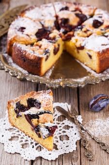 Pflaumenkuchen mit puderzucker und einer tasse kaffee