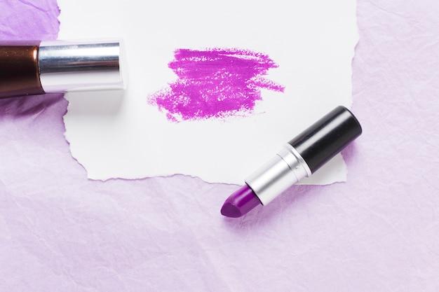 Pflaumenlippenstift mit abstrichen auf papierblatt und nagellack