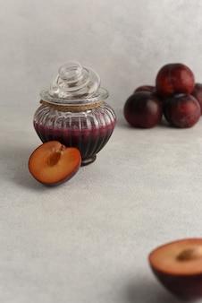 Pflaumenmarmelade in einer glasschüssel. natürliche hausgemachte marmelade in glasreliefglas und frischen pflaumenfrüchten.