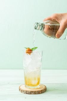 Pflaumensaft mit soda und pfefferminze auf holztisch. erfrischungsgetränk