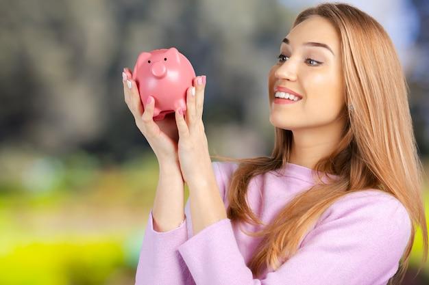Pflege für ersparnisse - frau mit einem sparschwein