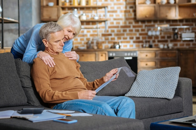 Pflege und unterstützung. nette, angenehm gealterte frau, die hinter ihrem ehemann steht und ihn umarmt, während sie ihre unterstützung zeigt