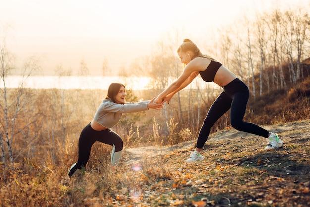 Pflege und unterstützung. sport lifestyle-konzept. junge starke frau, die ihrer freundin, morgen zusammen rüttelnd im sonnenschein hilft