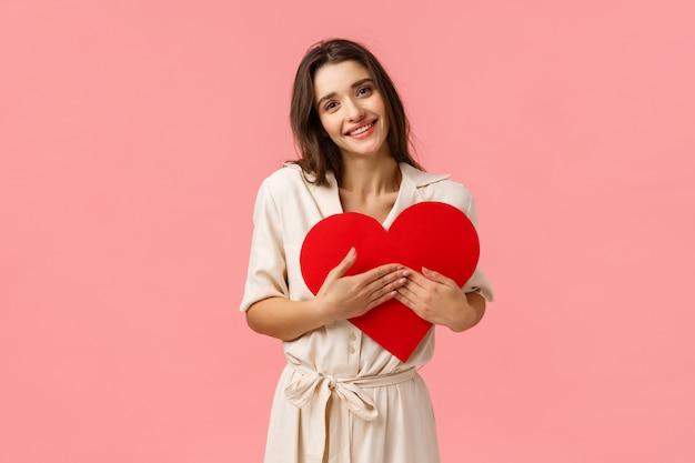 Pflege, zärtlichkeit und liebeskonzept. dumme charmante, verführerische frau im kleid, valentinskarte auf brust drückend, herzzeichen haltend und lächelnd berührt, zuneigungskamera schauend