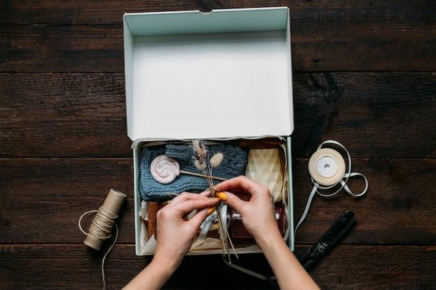 Pflegebox, paketideen. weibliche hände falten eine pflegebox mit süßigkeiten und kleidung. lieferung von pflegepaketen