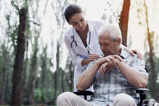 Pflegedoktor tröstet den traurigen alten mann