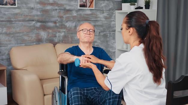 Pflegekraft, die einem älteren mann im rollstuhl bei der körperlichen therapie hilft. behinderte behinderte alte person, die professionelle hilfe krankenschwester, pflegeheimbehandlung und rehabilitation erholt