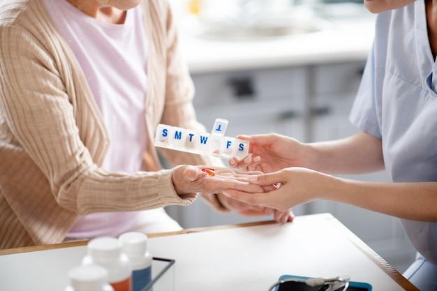 Pflegekraft, die pillen auf handfläche der frau im ruhestand setzt