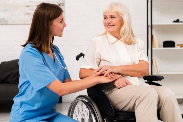 Pflegekraft, die um frau im rollstuhl sich kümmert