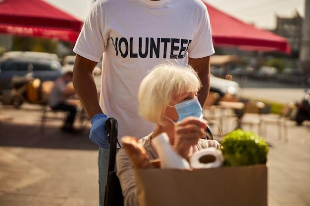 Pflegekraft führt eine alternde frau im rollstuhl bei ihren einkäufen durch die stadt