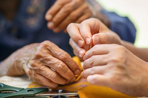 Pflegekraft hält faden die nadel für ältere frau in der stoffhandwerk ergotherapie