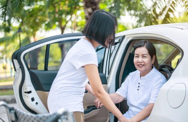Pflegekraft hilft älteren behinderten asiatischen frauen aus dem rollstuhl beim einsteigen ins auto