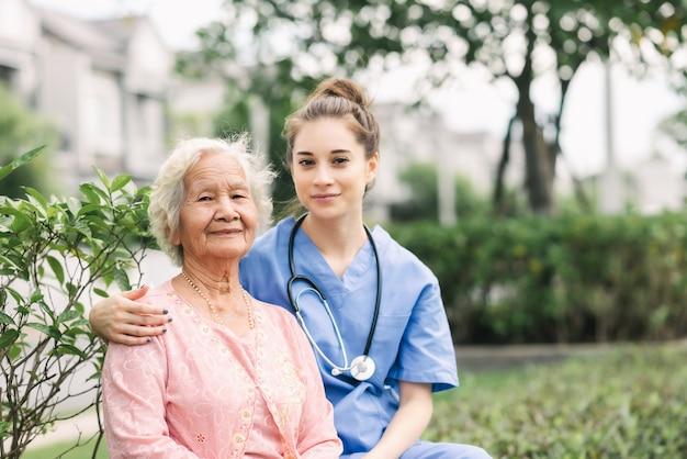 Pflegekraft krankenschwester mit älterer frau im freien