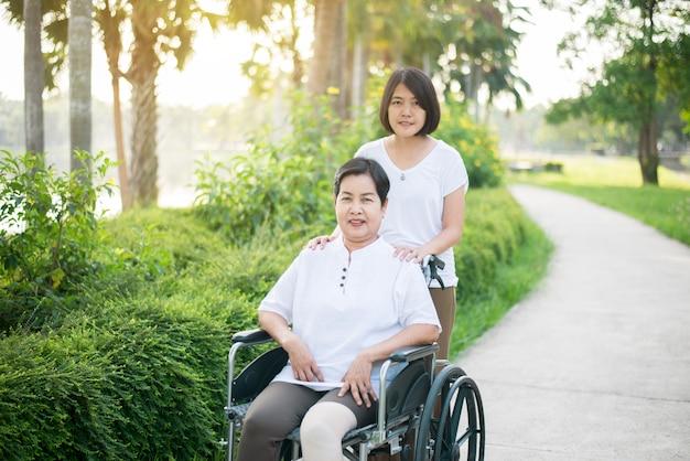 Pflegekraft kümmern sich um ältere asiatische frau, die auf rollstuhl am öffentlichen park, seniorenpflegeversicherungskonzept sitzt