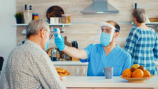 Pflegekraft mit waffenthermometer, die die körpertemperatur eines älteren mannes während des hausbesuchs misst. sozialarbeiter, die schutzbedürftige personen überprüfen, um die verbreitung von krankheiten zu verhindern