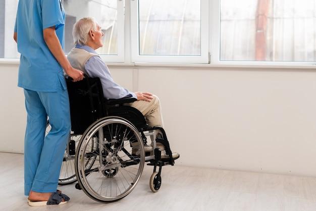 Pflegekraft und alter mann der hinteren ansicht, die auf dem fenster schauen