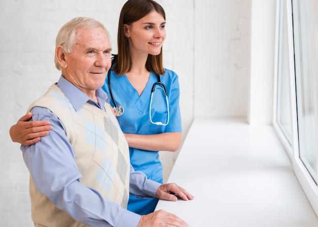 Pflegekraft und alter mann, die auf dem fenster schauen
