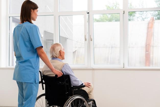 Pflegekraft und alter mann im rollstuhl, der auf dem fenster schaut