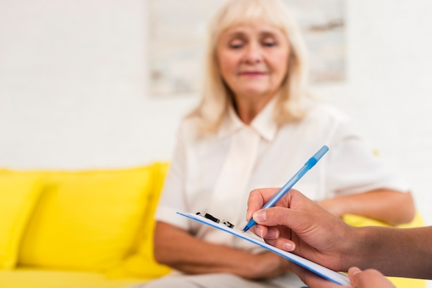 Pflegekraftschreiben auf klemmbrettnahaufnahme