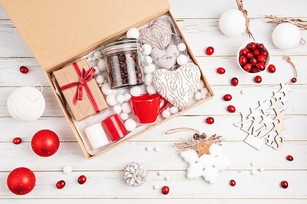 Pflegepaket, saisonale geschenkbox mit kaffee, kerzen und tasse in roten und weißen farben. personalisierter umweltfreundlicher korb für familie und freunde zu weihnachten. draufsicht, flach liegen