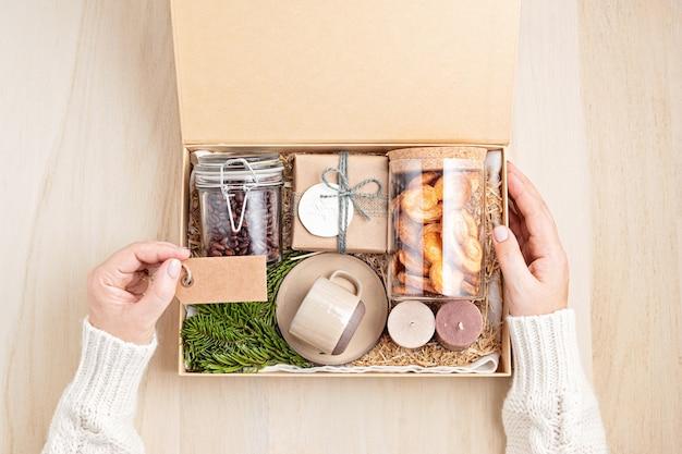 Pflegepaket und saisonale geschenkbox mit kaffee, keksen, kerzen und tasse vorbereiten