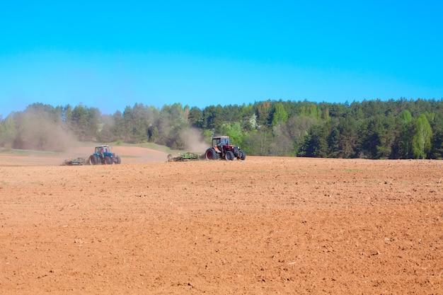 Pflugtraktor während des anbaus landwirtschaft arbeitet auf dem feld mit pflug
