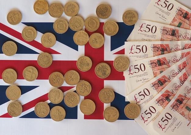 Pfund-münzen und banknoten, vereinigtes königreich über flagge over