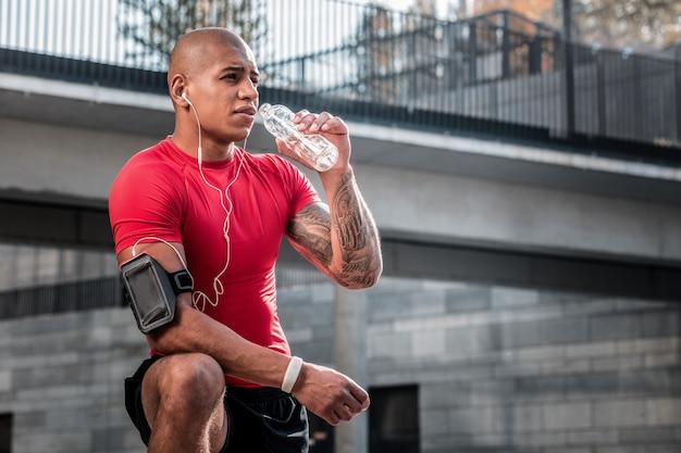 Ph-level. netter müder mann, der frisches kaltes wasser trinkt, während er nach dem training durstig ist