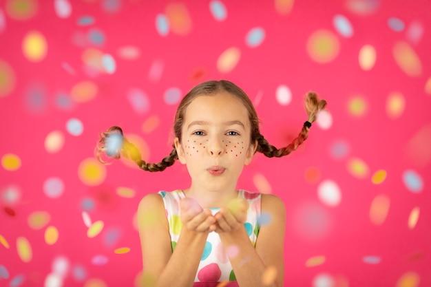 Phantasie kind mit zöpfen, die konfetti gegen rosa wand blasen.
