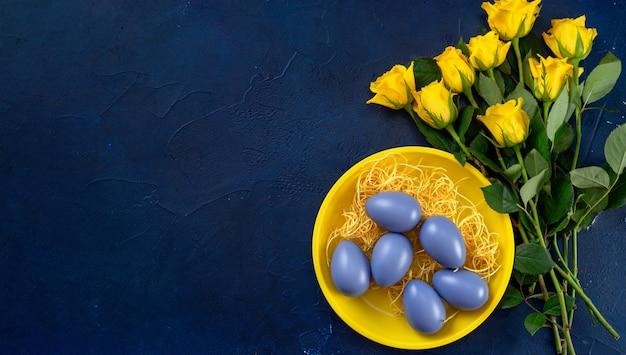 Phantomblaue farbe und gelbe rosen mit easte-eiern auf weinlesehintergrund