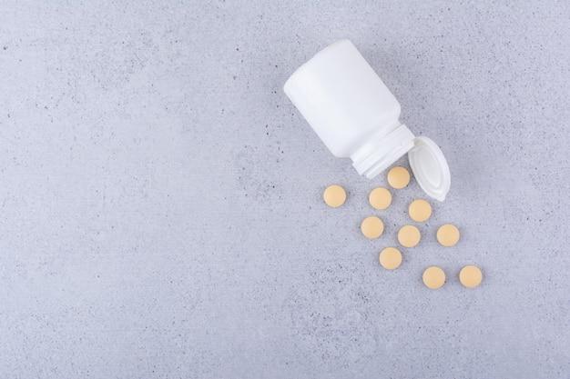 Pharmazeutische pillen aus weißem kunststoffbehälter. foto in hoher qualität