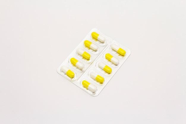 Pharmazeutische tabletten, gelbweiße kapseln in blisterpackung isoliert auf weißem hintergrund