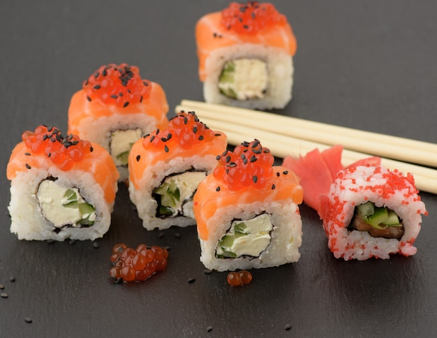 Philadelphia-sushi mit rotem kaviar auf einem schwarzen schieferbrett, nahaufnahme