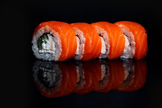 Philadelphia sushi roll auf einer schwarzen oberfläche mit reflexion.