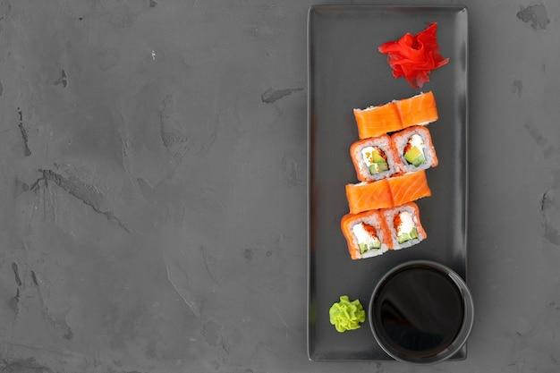 Philadelphia-sushi-rolle auf schwarzem hintergrund draufsicht, kopienraum