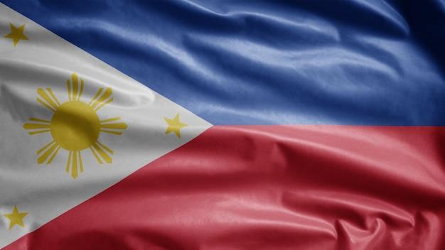 Philippinische flagge weht im wind. nahaufnahme des philippinischen fahnenblasens, weiche und glatte seide