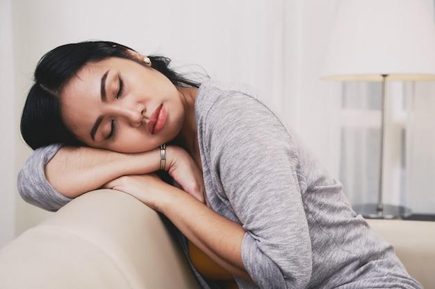 Philippinische frau, die auf sofa schläft