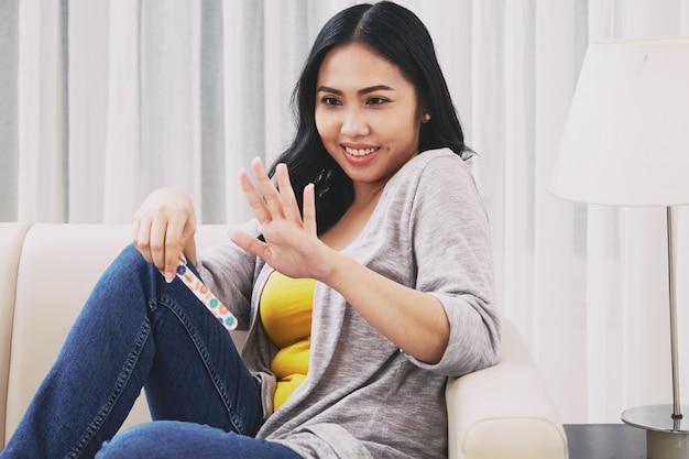 Philippinische frau, die fingernägel betrachtet